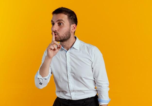 気になるハンサムな男は、オレンジ色の壁に隔離された側を見て静かなサインを身振りで示す口に指を置きます