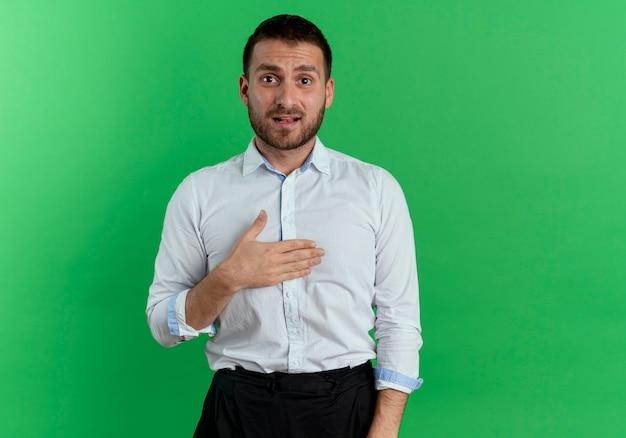 L'uomo bello ansioso mette la mano sul mento isolato sulla parete verde