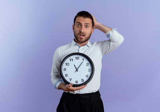 L'uomo bello ansioso mette la mano sulla testa dietro l'orologio della tenuta isolato sulla parete viola