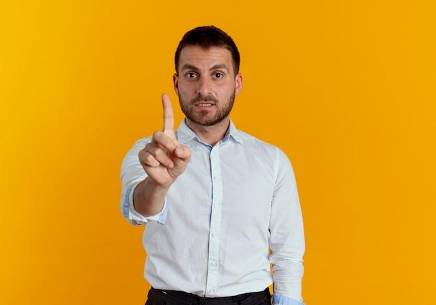 불안 잘 생긴 남자는 오렌지 벽에 고립 된 검지 손가락을 보여줍니다