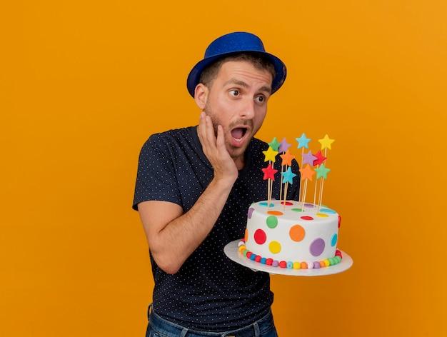 L'uomo bello ansioso che porta il cappello blu del partito tiene la torta di compleanno che esamina il lato isolato sulla parete arancione
