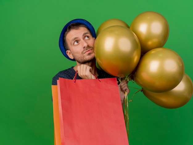 Обеспокоенный красавец в синей шляпе держит гелиевые шары и бумажные пакеты для покупок, глядя вверх изолированно на зеленой стене