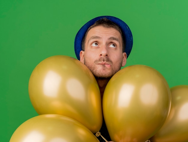 Обеспокоенный красавец в синей шляпе держит гелиевые шары, глядя вверх, изолированные на зеленой стене