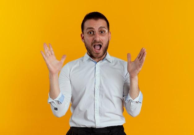 Uomo bello ansioso con vetri ottici solleva le mani isolate sulla parete arancione