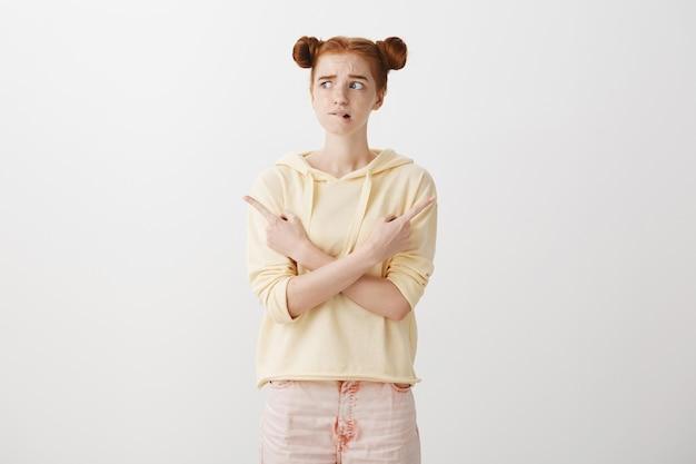 Тревожная нерешительная рыжая девушка стоит перед выбором, указывая пальцами в сторону