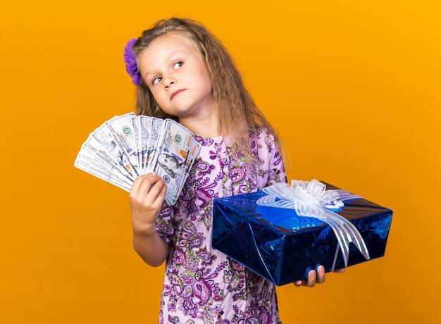 Ansiosa bambina bionda con confezione regalo e denaro guardando il lato isolato sulla parete arancione con spazio copia