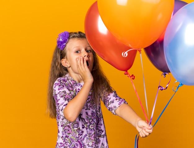 Ansiosa bambina bionda che tiene palloncini di elio e mette la mano sul viso isolato sulla parete arancione con spazio di copia