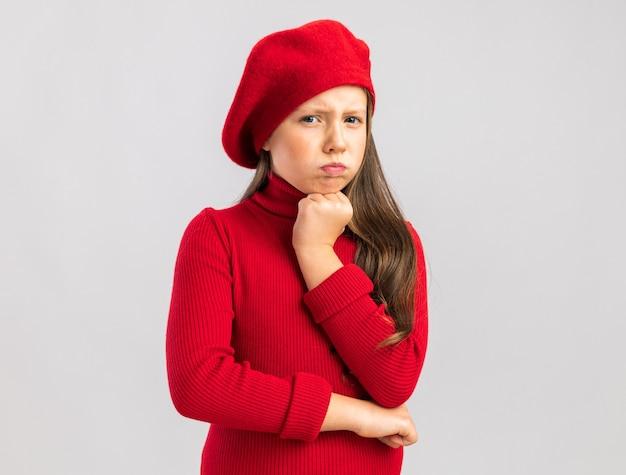 コピースペースで白い壁に隔離されたあごに手を保つ赤いベレー帽を身に着けている気になる小さなブロンドの女の子