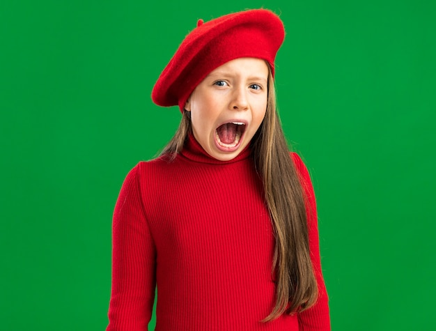 Anxious little blonde girl wearing red beret looking at camera and scream isolated on green wall with copy space