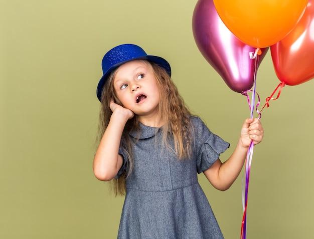 Ansiosa bambina bionda con cappello da festa blu che tiene palloncini di elio e guarda il lato isolato sulla parete verde oliva con spazio di copia