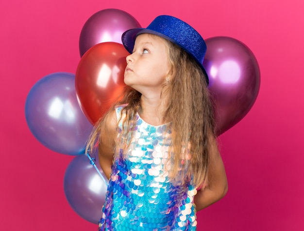 Anxious little blonde girl with blue party hat holding helium balloons and looking at side isolated on pink wall with copy space
