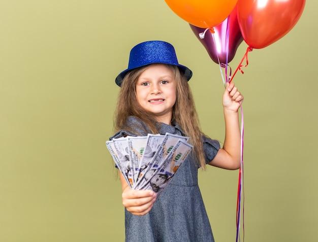 Ansiosa bambina bionda con cappello blu del partito che tiene palloncini di elio e denaro isolato sulla parete verde oliva con lo spazio della copia