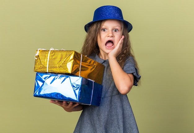 Anxious little blonde girl with blue party hat putting hand on face and holding gift boxes isolated on olive green wall with copy space