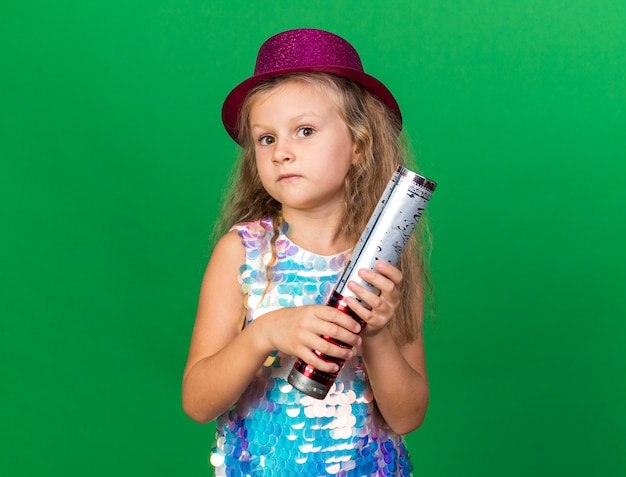 Anxious little blonde girl with purple party hat holding confetti cannon isolated on green wall with copy space