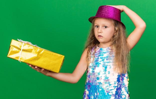Ansiosa bambina bionda con cappello da festa viola che tiene in mano una confezione regalo e mette la mano sul cappello isolato sulla parete verde con spazio per le copie