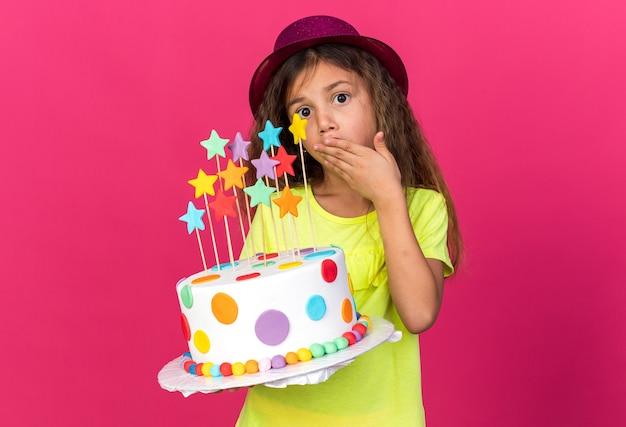 Ansiosa bambina caucasica con cappello da festa viola che mette la mano sulla bocca e tiene la torta di compleanno isolata sulla parete rosa con spazio per le copie