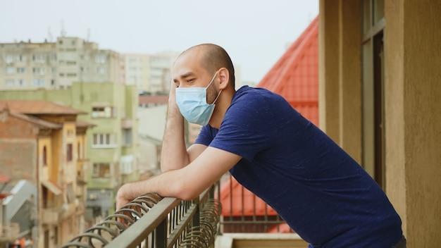 コロナウイルスのパンデミックの間にテラスでマスクを持つ気になる男。