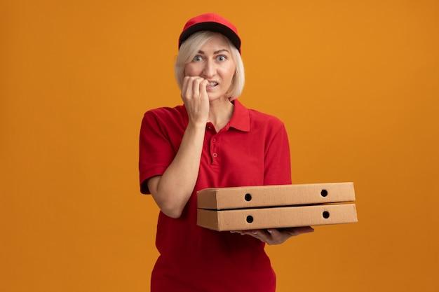 Ansiosa donna di mezza età bionda consegna in uniforme rossa e berretto che tiene i pacchetti di pizza guardando le dita mordaci davanti isolate sulla parete arancione con spazio di copia