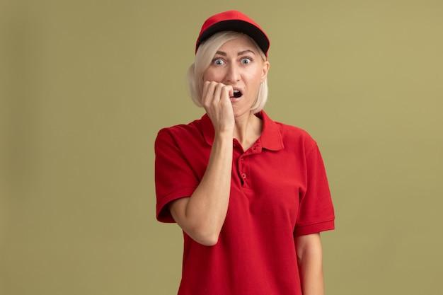 Donna di consegna bionda di mezza età ansiosa in uniforme rossa e berretto che mette la mano sulla bocca