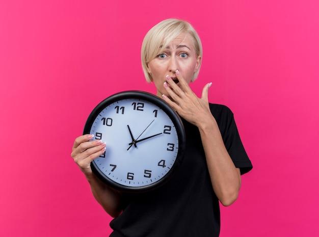 Ansiosa donna slava bionda di mezza età che tiene l'orologio che tiene la mano sulla bocca isolata sulla parete cremisi