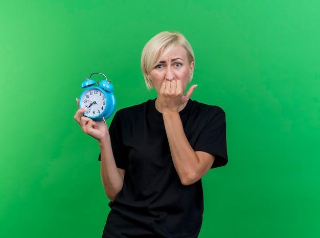 Тревожная блондинка средних лет, смотрящая вперед, держит будильник, кусая пальцы, изолированную на зеленой стене