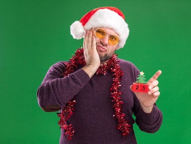 緑の背景に分離されたカメラを見て顔に手を保ちながらクリスマスツリーのおもちゃを保持しているメガネと首の周りにサンタの帽子と見掛け倒しの花輪を身に着けている気になる中年男性