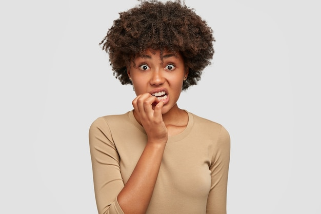 Anxious nervous african american female bites finger nails with puzzled expression, has curly dark hair, dressed casually, isolated over white wall. omg, i am afraid of this! emotions concept