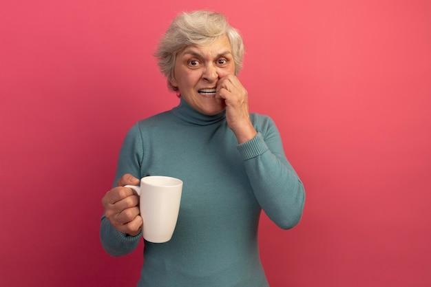 Anziana ansiosa che indossa un maglione blu a collo alto che tiene una tazza di tè che tocca la bocca che mostra i denti isolati sulla parete rosa con spazio di copia