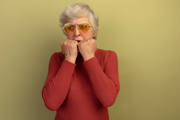 빨간 터틀넥 스웨터와 선글라스를 쓴 불안한 노부인이 복사공간이 있는 올리브 녹색 벽에 격리된 입에 손을 대고 옆을 바라보고 있다