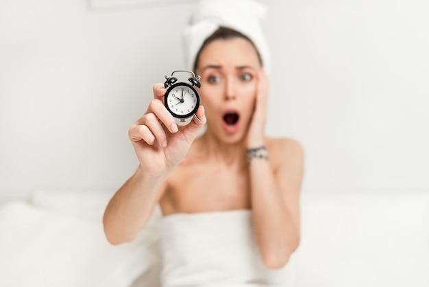 Взволнованная проспавшая женщина в постели держит будильник в руке и кричит в постели спальни