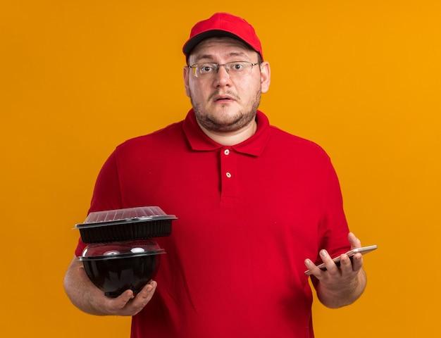 Giovane fattorino in sovrappeso ansioso in occhiali ottici che tengono contenitori per alimenti e telefono isolato su parete arancione con spazio di copia