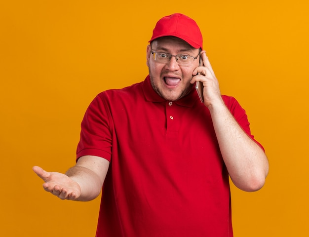 Ansioso sovrappeso giovane fattorino in occhiali ottici parlando al telefono isolato sulla parete arancione con spazio copia