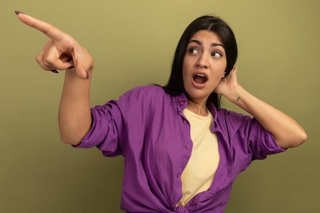 La ragazza caucasica piuttosto mora ansiosa mette la mano sulla testa dietro guardando e indicando a lato su verde oliva