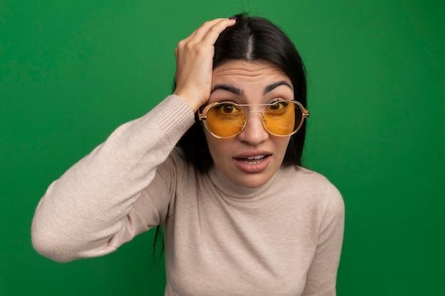 Ansiosa ragazza caucasica bella mora in occhiali da sole mette la mano sulla testa sul verde