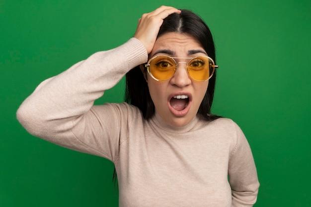 Ansiosa ragazza caucasica bella mora in occhiali da sole mette la mano sulla testa e guarda la telecamera sul verde