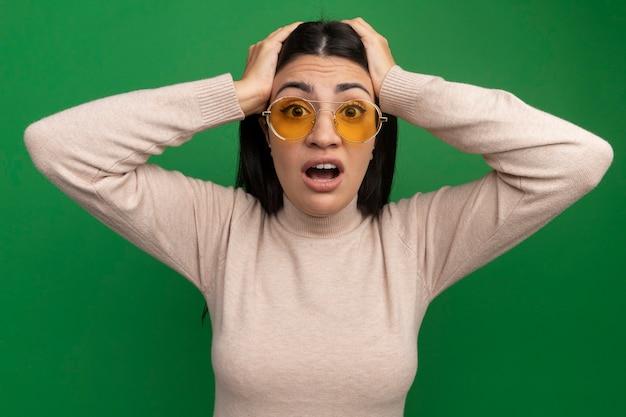 Ansiosa ragazza caucasica bella mora in occhiali da sole mette le mani sulla testa sul verde