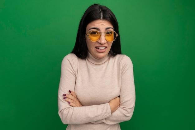 Ansiosa ragazza caucasica bella mora in occhiali da sole si leva in piedi con le braccia incrociate sul verde