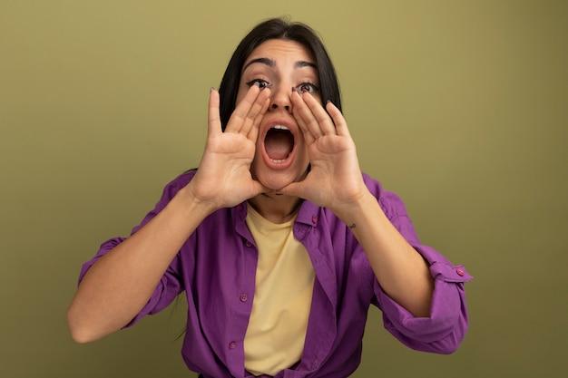 La donna caucasica abbastanza castana ansiosa tiene le mani vicino alla bocca isolata