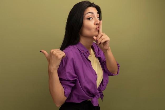 Donna graziosa ansiosa del brunette che fa gesto di silenzio e punti a lato isolato sulla parete verde oliva