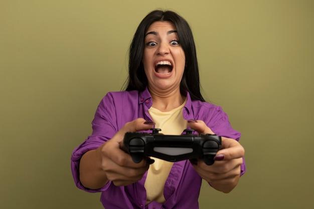 Обеспокоенная симпатичная брюнетка женщина держит и смотрит на игровой контроллер, изолированный на оливково-зеленой стене