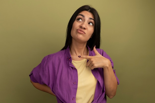 Обеспокоенная симпатичная брюнетка женщина указывает в сторону и смотрит вверх изолированно на оливково-зеленой стене