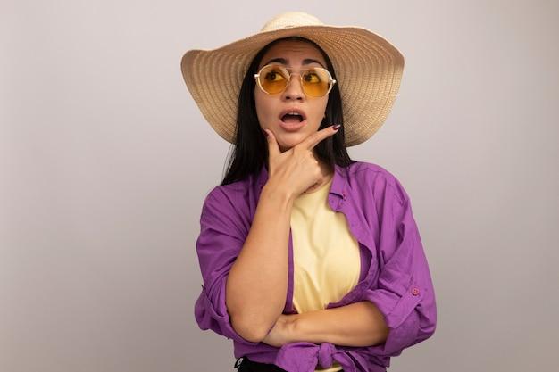 La donna ansiosa graziosa del brunette in occhiali da sole con il cappello della spiaggia tiene il mento e guarda al lato isolato sulla parete bianca