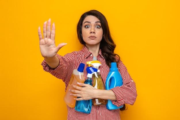 Donna caucasica ansiosa delle pulizie che allunga la mano gesticolando il segnale di stop e tiene in mano spray e liquidi per la pulizia