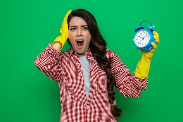Donna caucasica ansiosa delle pulizie con guanti di gomma che si mette la mano sulla testa e tiene la sveglia