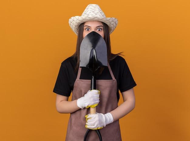 복사 공간이 있는 주황색 벽에 격리된 얼굴 앞에 삽을 들고 정원용 모자와 장갑을 끼고 있는 불안한 백인 여성 정원사