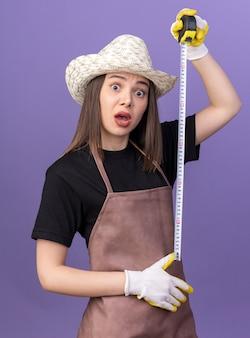 Giardiniere femminile piuttosto caucasico ansioso che indossa cappello e guanti da giardinaggio che tengono il metro a nastro isolato sulla parete viola con spazio di copia