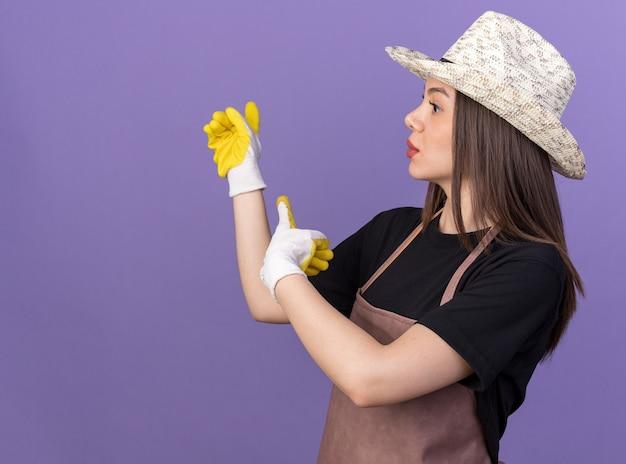 Giardiniere femmina caucasica piuttosto ansioso che indossa cappello e guanti da giardinaggio che puntano indietro guardando a lato