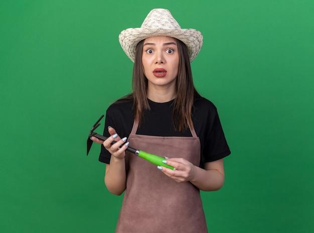 복사 공간이 있는 녹색 벽에 격리된 괭이 갈퀴를 들고 원예용 모자를 쓰고 있는 불안한 백인 여성 정원사