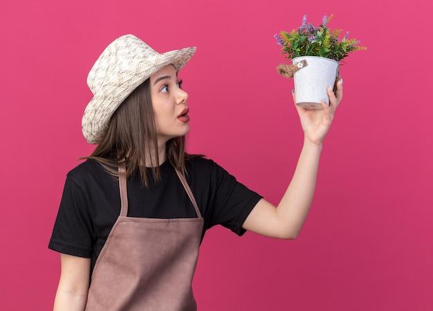 Giardiniere femmina piuttosto caucasico ansioso che indossa cappello da giardinaggio che tiene e guarda il vaso di fiori isolato sulla parete rosa con spazio di copia