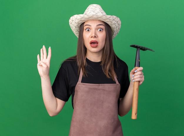 갈퀴를 들고 원예용 모자를 쓰고 복사 공간이 있는 녹색 벽에 격리된 손가락으로 4개의 몸짓을 하는 불안한 백인 여성 정원사